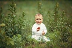 Chłopiec obsiadanie w trawie z truskawką Fotografia Stock