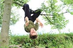 Chłopiec obwieszenie na drzewie Obrazy Royalty Free