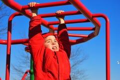 Chłopiec obwieszenie na Małpich barach fotografia stock