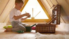 Chłopiec odkrywa zawartość klatka piersiowa z zabawkami w attyku zdjęcie wideo