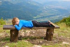 Chłopiec odpoczywa na ławce Obrazy Royalty Free