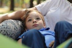 Chłopiec odpoczywa na macierzystej nodze Zdjęcie Royalty Free