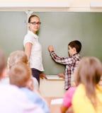 Chłopiec odpowiada pytania nauczyciele blisko zarządu szkoły Fotografia Stock