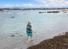 Chłopiec odprowadzenie przez płytkiej wody morskiej obok myjący w górę s Zdjęcie Royalty Free