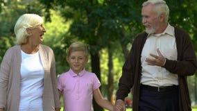 Chłopiec odprowadzenie z jego dziadkami w parku, cieszy się szczęśliwego czas wpólnie zbiory