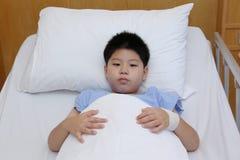Chłopiec odzieży cierpliwy kostium w łóżku szpitalnym Fotografia Stock