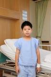 Chłopiec odzieży kostiumu cierpliwa pozycja przed łóżkiem szpitalnym Zdjęcia Royalty Free