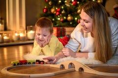 Chłopiec ogląda jego mamy bawić się z zabawka pociągiem fotografia stock
