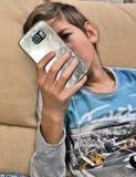 Chłopiec ogląda jego telefon komórkowego Zdjęcia Royalty Free