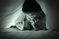 Chłopiec ogląda online parawanową pastylkę, pod duvet Zdjęcie Stock