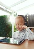 Chłopiec ono uśmiecha się w zachwycie słucha muzyka obraz royalty free