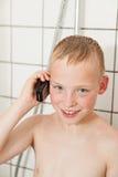 Chłopiec opowiada w telefonie podczas gdy brać prysznić Obraz Stock