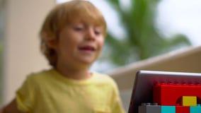 Chłopiec opowiada z przyjaciółmi i rodziną na wideo wezwaniu w zwrotnikach używać pastylkę i radio hełmofony zbiory wideo
