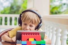 Chłopiec opowiada z przyjaciółmi i rodziną na wideo wezwaniu w zwrotnikach używać pastylkę i radio hełmofony obraz royalty free