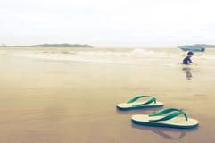 Chłopiec opuszczał jego buty na plaży zdjęcie royalty free