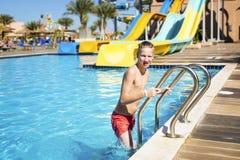 Chłopiec opuszcza basenu po pływać Fotografia Stock
