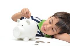 Chłopiec oszczędzania pieniądze w prosiątko banku Obraz Royalty Free
