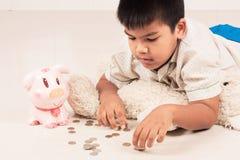 chłopiec oszczędzania pieniądze w prosiątko banku zdjęcia stock