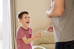 Chłopiec otrzymywa kieszeniowego pieniądze od ojca (tolerowanie) Zdjęcia Royalty Free