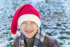 Chłopiec outside będący ubranym trykotową Santa nakrętkę, śmiający się i scrunching, Zdjęcia Stock