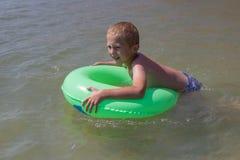 Chłopiec pływa na nadmuchiwanym okręgu, szczęśliwa roześmiana chłopiec cieszy się pływać w morzu Obraz Stock