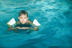 Chłopiec pływa w pływackim basenie podczas pływackiej lekci obraz stock