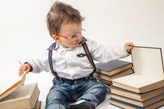 Chłopiec patrzeje książkę z eyeglasses Obraz Stock