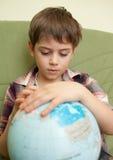 Chłopiec patrzeje kulę ziemską Fotografia Royalty Free