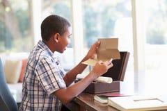 Chłopiec Patrzeje list W Keepsake pudełku Na biurku fotografia royalty free