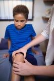 Chłopiec patrzeje podczas gdy żeński terapeuta masowania kolano zdjęcie royalty free