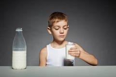 Chłopiec patrzeje szkło mleko zdjęcia royalty free