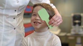 Chłopiec patrzeje wzroku test z jeden okiem zakrywającym z occluder Obrazy Stock