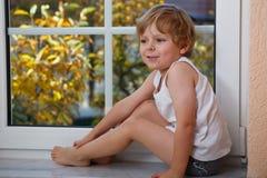 Chłopiec patrzeje z okno na żółtym au trzy roku Fotografia Stock
