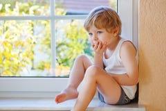 Chłopiec patrzeje z okno na żółtym au trzy roku Zdjęcia Royalty Free