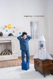 Chłopiec patrzeje zabawki rakietę indoors w piżamach Obraz Royalty Free