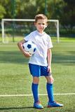 Chłopiec piłki nożnej gracz futbolu z piłką na zielonej trawie Obraz Royalty Free