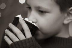Chłopiec pije kakao z marshmallows bokeh wygodnym tłem Biały zdjęcie stock