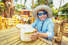 Chłopiec pije kokosowego koktajl na tropikalnej miejscowości nadmorskiej zdjęcie royalty free