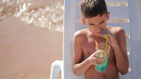 Chłopiec pije koktajl na tropikalnej plaży zdjęcie wideo