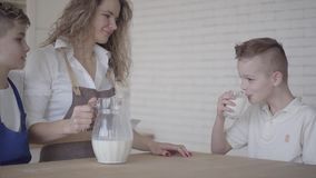 Chłopiec pije mleko podczas gdy siedzący przy stołem obok jego brata w kuchni i matki bractwo rodzina zbiory