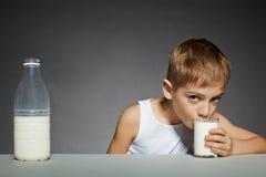 Chłopiec pije szkło mleko fotografia stock