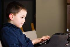 Chłopiec pisać na maszynie na starym maszyna do pisania obraz royalty free