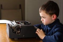 Chłopiec pisać na maszynie na starym maszyna do pisania zdjęcie royalty free