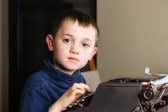 Chłopiec pisać na maszynie na starym maszyna do pisania Fotografia Royalty Free