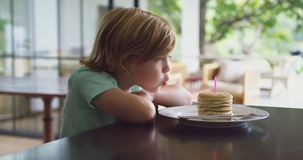 Chłopiec podmuchowa świeczka na blinie przy łomotać stół w kuchni 4k w domu zbiory