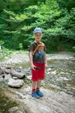 Chłopiec podróżnik przechodzi strumienia bród zdjęcia royalty free