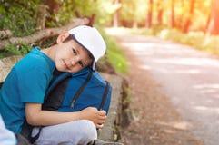 Chłopiec podróżnik z plecakiem i nakrętką siedzi drogą obraz royalty free