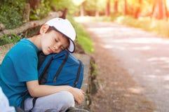 Chłopiec podróżnik z plecakiem i nakrętką siedzi drogą zdjęcie royalty free