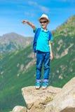 chłopiec podróżnika stojaki na skale i pokazują up obraz royalty free