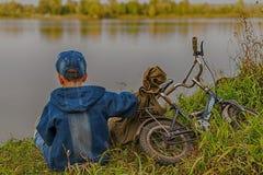 Chłopiec podróżuje z plecakiem na brzeg rzeki Zdjęcia Royalty Free